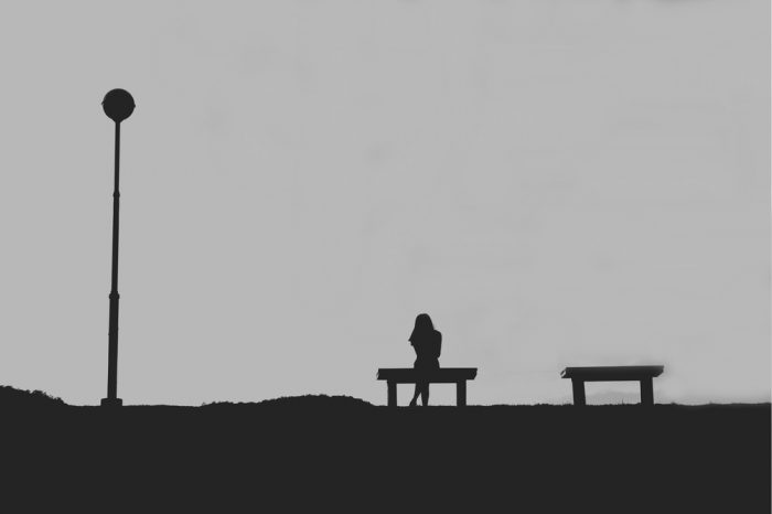 Чорно-біле фото дівчини сидить на лавочці