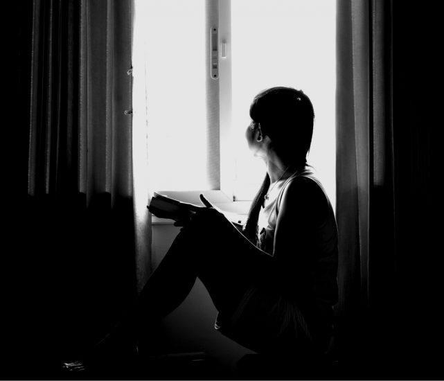 Чорно-біле фото дівчини сидить на підлозі і дивилася у вікно