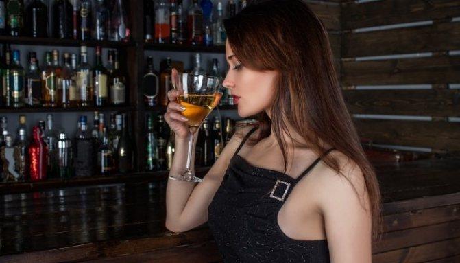 Дівчина випиває за барною стійкою