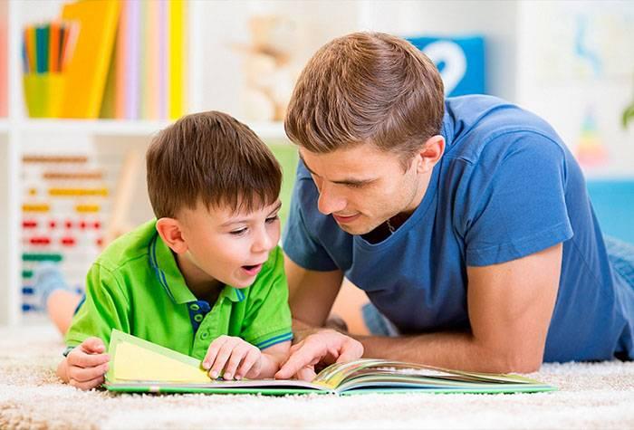 Папа дивиться з дитиною книжку